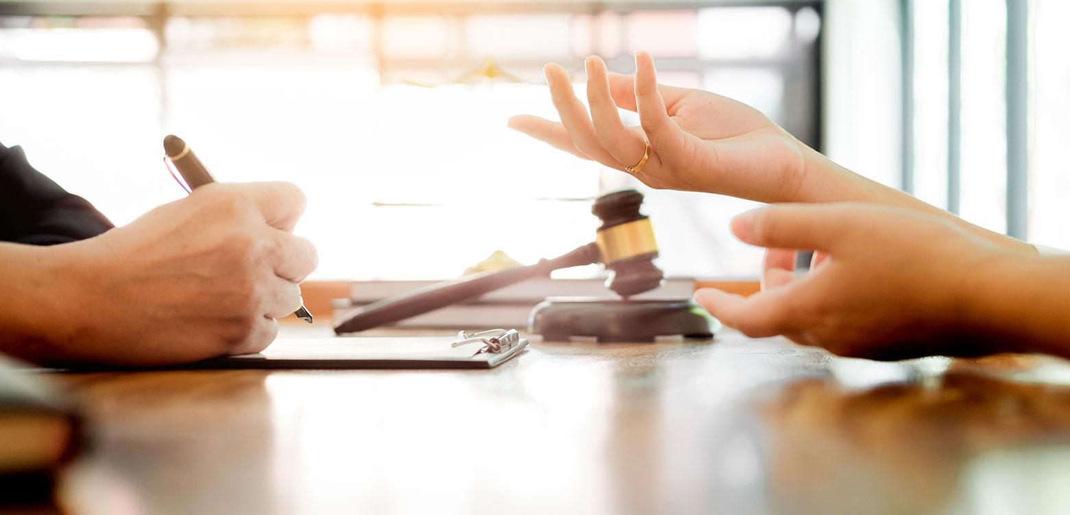 peoples hands over a desk talking